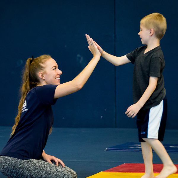 usa youth fitness center coach high fiving student